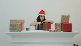 At the table, woman in the hood cuts off excess tape on a gift. stock footage