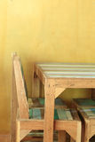 Table wood in yellow room with mortar wall Royalty Free Stock Photography