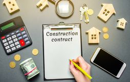 Table with wooden houses, calculator, coins, magnifying glass with the word Construction contract. Planning the construction of royalty free stock image