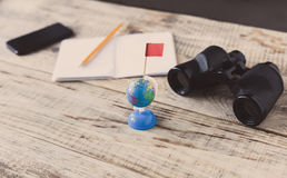 Table wooden planks, smartphone, nootbook, pencil, Globe, binoculars, flag, aim, achieving, target, tourism, travel. Tourism. Hips Stock Photography
