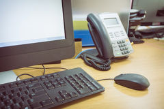Table work in office with telephone and computer Royalty Free Stock Image