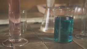 On table is worth chemical glassware and glass jar with an inscription in Latin close up. On ceramic surface of the table located volumetric flasks, bottles stock footage