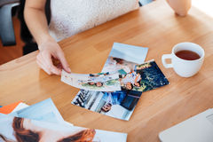 Table of young woman photographer drinking tea and choosing photos Royalty Free Stock Photo