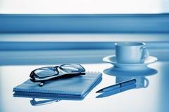 Tableau à côté de la fenêtre avec le carnet et les verres Photographie stock libre de droits