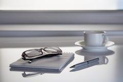 Tableau à côté de la fenêtre avec un carnet et des verres Photo stock