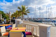 Tableau avec des chaises dans le restaurant dans la marina de Puerto Calero Photographie stock libre de droits
