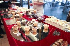 Tableau avec des petits gâteaux et des gâteaux Images stock