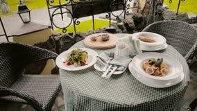 Tableau avec des plats dans un café sur la rue banque de vidéos