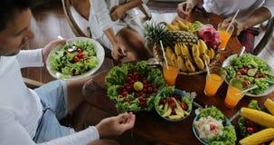 Tableau avec des plats du groupe de personnes de fruits tropicaux et de vue d'angle supérieur de salade mangeant de la nourriture
