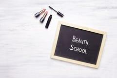 Tableau avec l'école de beauté écrite là-dessus, et produc cosmétique Image stock