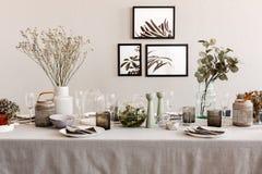 Tableau avec l'ensemble élégant pour le dîner, intérieur avec des affiches sur le mur image stock