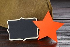 Tableau avec l'espace vide, le chapeau militaire et l'étoile rouge sur un bois Photographie stock libre de droits
