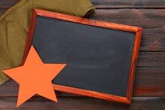 Tableau avec l'espace vide, le chapeau militaire et l'étoile rouge sur un bois Photo libre de droits