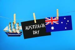 Tableau avec l'inscription : Jour heureux d'Australie entouré par des constructeurs de navires, une boussole, une horloge et un d Images stock