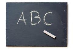 Tableau avec la craie et les lettres A, B, C, sur le blanc Photographie stock
