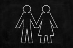 Tableau avec le dessin de l'homme et de femme tenant la main Photographie stock libre de droits