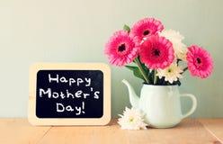 Tableau avec le jour de mères heureux d'expression devant le champ des fleurs Image libre de droits