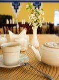 Tableau avec le thé à un arrière-plan de restaurant, fleurs images stock