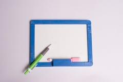 Tableau blanc encadré par bleu avec un stylo vert Photo stock