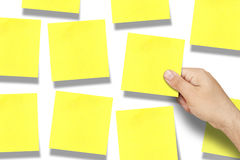Tableau blanc jaune vide de post-it de post-it de main Photographie stock libre de droits