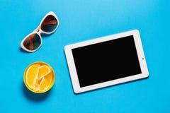 Tableau créatif d'espace de travail avec la Tablette blanche et les oranges lumineuses de lunettes de soleil sur l'espace bleu de Photos stock