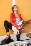 Tableau de With Leg On de chanteuse jouant la guitare Photographie stock