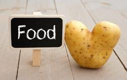 Tableau de nourriture avec la pomme de terre en forme de coeur Images libres de droits