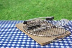 Tableau de pique-nique avec la nappe à carreaux, planche à découper, gril et Photos stock