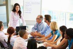 Tableau de salle de réunion d'Addressing Meeting Around de femme d'affaires images libres de droits