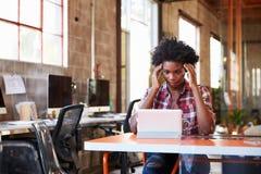 Tableau de Sits At Meeting de concepteur travaillant à la Tablette de Digital photos stock