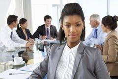 Tableau de Sitting Around Boardroom de femme d'affaires avec des collègues photos stock