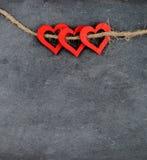 Tableau de vintage avec trois symboles rouges de forme de coeur sur la corde Images libres de droits