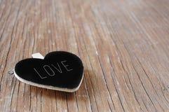 Tableau en forme de coeur avec l'amour de mot sur le su en bois rustique Images libres de droits