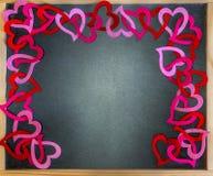 Tableau encadré par des coeurs de coupe-circuit de feutre de rouge et de rose, l'espace Images libres de droits