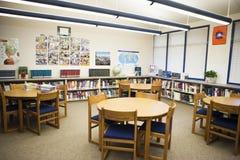 Tableau et chaises disposés dans la bibliothèque de lycée Image libre de droits