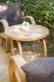 Tableau et chaises se tenant dans le jardin avec des ombres Images stock