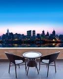 Tableau et chaises sur une terrasse, vue sur une ville Images stock