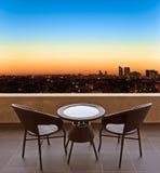 Tableau et chaises sur une terrasse, vue sur une ville Photographie stock libre de droits