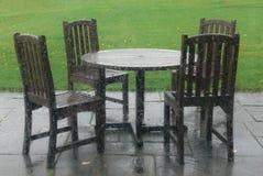 Tableau et présidences sur un patio vide un jour pluvieux Images stock