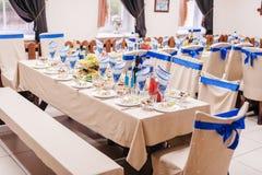 Tableau mis pour une nappe blanche de partie nuptiale et des chaises de rubans blancs et bleus photographie stock libre de droits