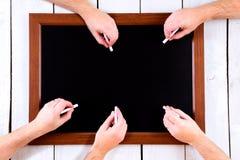 Tableau noir avec beaucoup de mains avec la craie Photo libre de droits