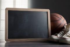 Tableau noir avec des chaussures et le basket-ball de toile Photo stock