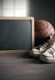 Tableau noir avec des chaussures et le basket-ball de toile Photographie stock libre de droits
