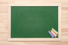 Tableau noir avec des crayons Photographie stock libre de droits