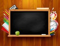 Tableau noir avec des fournitures scolaires sur le backgrou en bois Image libre de droits