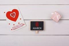 Tableau noir avec l'étiquette du 8 mars, un cadeau et une carte avec les coeurs rouges Photos stock