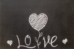Tableau noir avec l'amour de mot écrit là-dessus Photo libre de droits