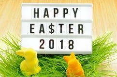 Tableau noir avec l'inscription Joyeuses Pâques 2018 dans Joyeuses Pâques allemandes 2018, symbole dollar, bouquet des fleurs et  Image stock