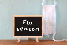 Tableau noir avec la saison de la grippe d'expression écrite sur lui et le masque protecteur Image stock