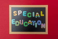 Tableau noir avec le cadre en bois, éducation spéciale des textes dans les lettres colorées, fond rouge de mur photographie stock libre de droits
